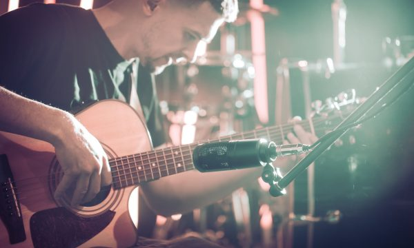 The Studio microphone records an acoustic guitar close-up, in a recording Studio or concert hall, with a drum set on a background in out-of-focus mode. Beautiful blurred background of colored lanterns