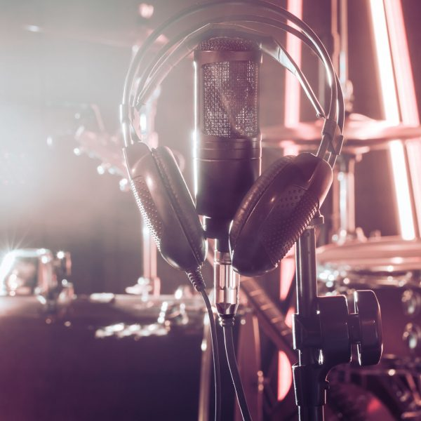 Studio microphone and headphones on a close-up stand, in a recording Studio or concert hall, with a drum set in the background in out-of-focus mode. Beautiful blurred background of colored lights.